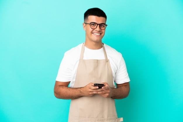 Kellner im restaurant über isoliertem blauem hintergrund, der eine nachricht mit dem handy sendet