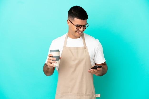 Kellner im restaurant über isoliertem blauem hintergrund, der kaffee zum mitnehmen und ein handy hält