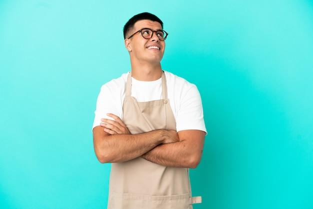 Kellner im restaurant über isoliertem blauem hintergrund, der lächelnd nach oben schaut