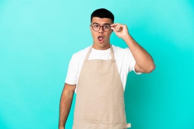 Kellner im restaurant über isoliertem blauem hintergrund mit brille und überrascht?
