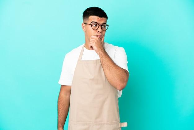 Kellner im restaurant über isoliertem blauem hintergrund mit zweifeln und verwirrendem gesichtsausdruck