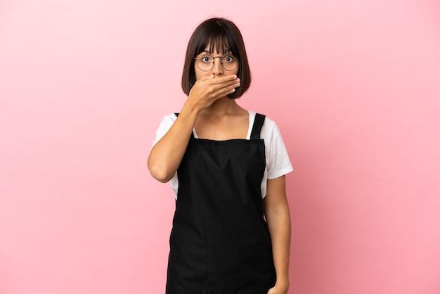 Kellner im restaurant über isoliertem rosa hintergrund, der den mund mit der hand bedeckt