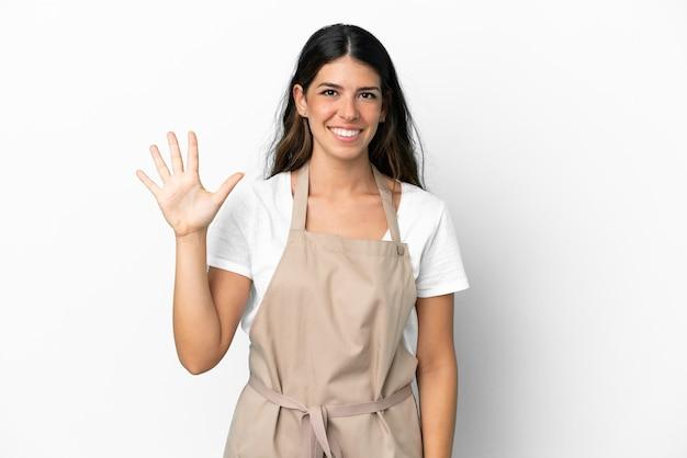 Kellner im restaurant über isoliertem weißem hintergrund, der mit den fingern fünf zählt