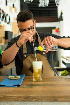 Kellner in der kneipe oder im restaurant, die ein gin tonic cocktail zubereiten.