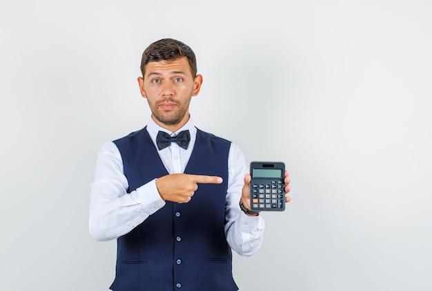 Kellner in hemd, weste, fliege, zeigt auf taschenrechner, vorderansicht.