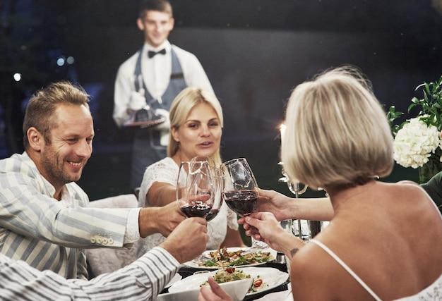 Kellner ist für ihre bestellung. eine gruppe erwachsener freunde ruht sich abends im hinterhof des restaurants aus und unterhält sich