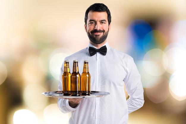Kellner mit bierflaschen auf dem tablett auf unfokussiertem hintergrund