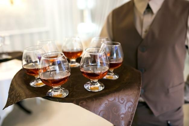 Kellner mit einem tablett begrüßt besucher, gefüllte gläser cognac