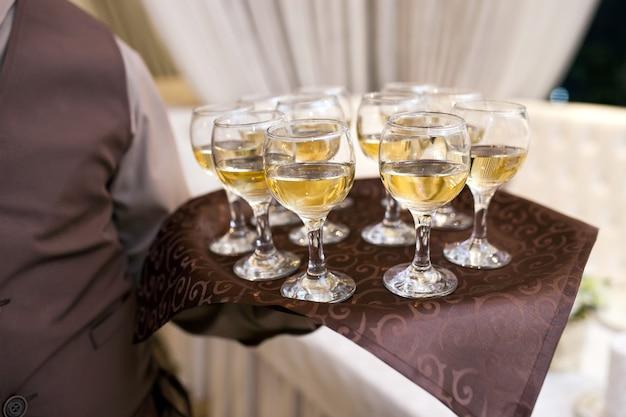 Kellner mit einem tablett begrüßt besucher, gefüllte gläser wein