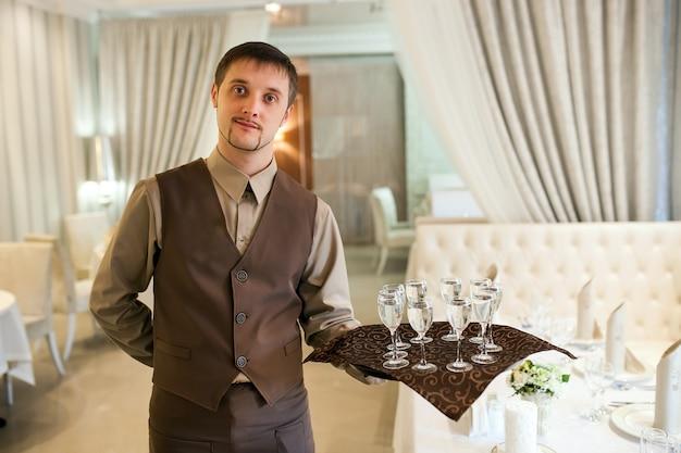 Kellner mit einem tablett begrüßt besucher