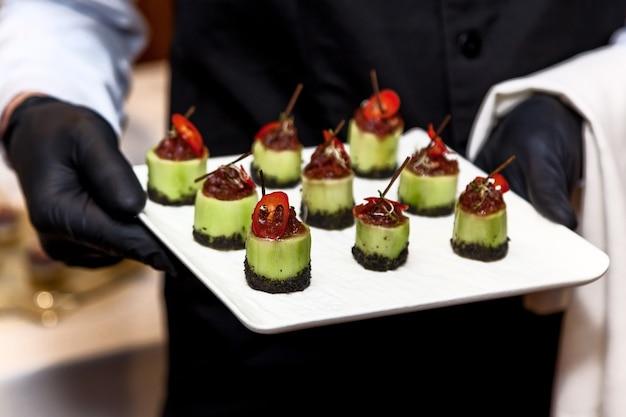 Kellner mit schwarzen handschuhen trägt snacks bei einer weihnachtsfeier oder hochzeitsfeier