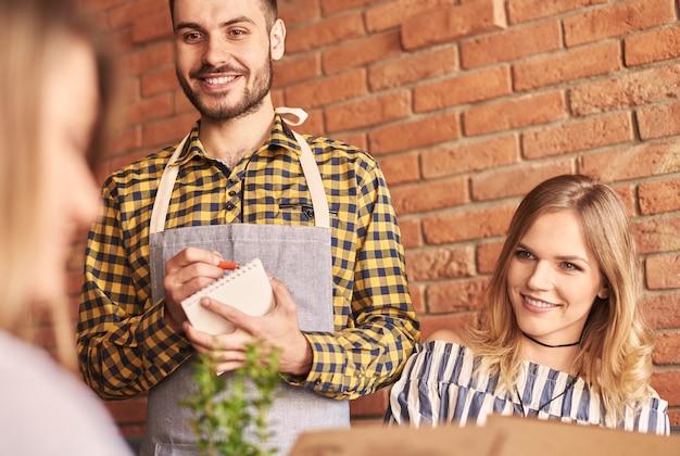 Kellner nimmt bestellungen von kunden entgegen