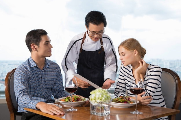 Kellner offering paar hauptgerichte in restaurant