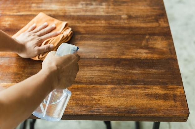 Kellner-reinigungstisch mit desinfektionsspray zum schutz der infektion covid-19 im café.