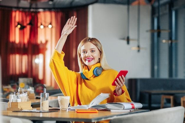 Kellner rufen blonde stilvolle frau, die ihre hand hebt, während sie nach kellner ruft