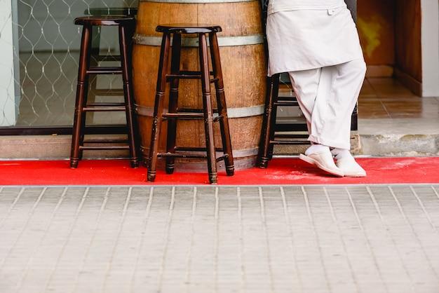 Kellner ruht auf der terrasse seines italienischen restaurants und wartet auf kunden.