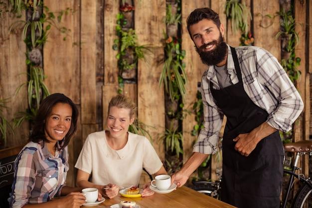 Kellner serviert dem kunden eine tasse kaffee