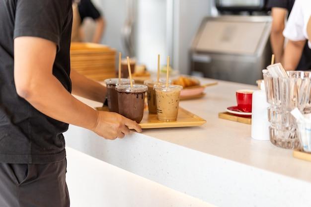 Kellner serviert dem kunden eiskaffee und eisschokolade auf holztablett