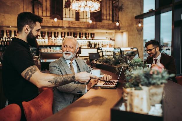 Kellner serviert den geschäftsleuten im restaurant kaffee.