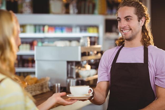 Kellner serviert eine tasse kaffee an der theke