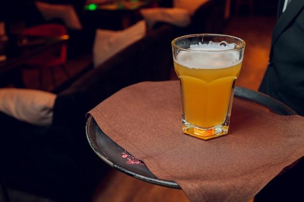Kellner serviert gläser kaltes bier auf dem tablett.