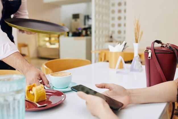Kellner serviert kaffee und dessert