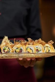 Kellner serviert köstliches avocado-sushi