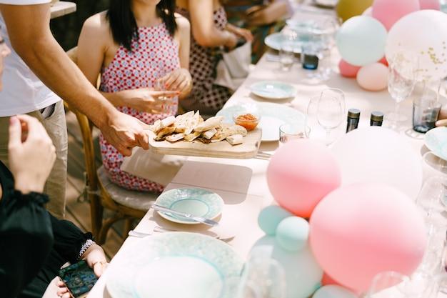 Kellner serviert snacks an die leute, die am bedienten tisch sitzen