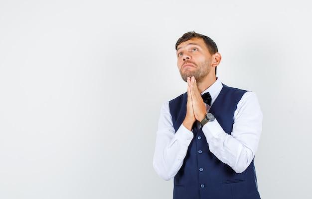 Kellner stützt kinn auf hände in betender geste in hemd, weste und hoffnungsvoll, vorderansicht.