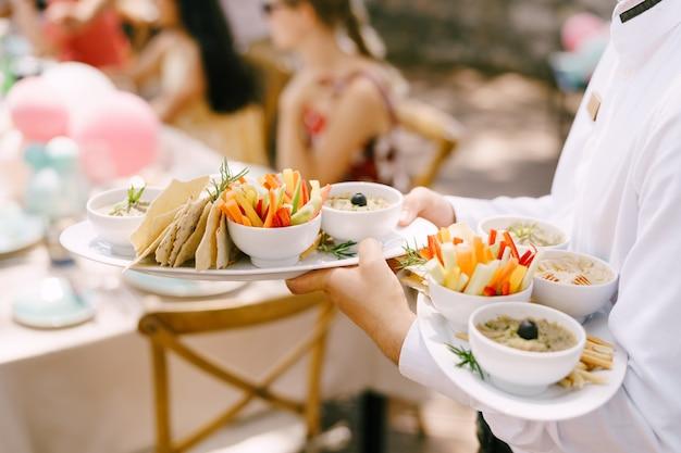 Kellner trägt verschiedene gerichte auf den tellern zu den gästen am tisch
