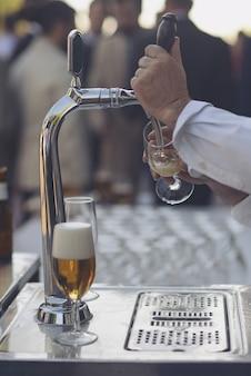 Kellner wirft bier auf einen openair-barhahn