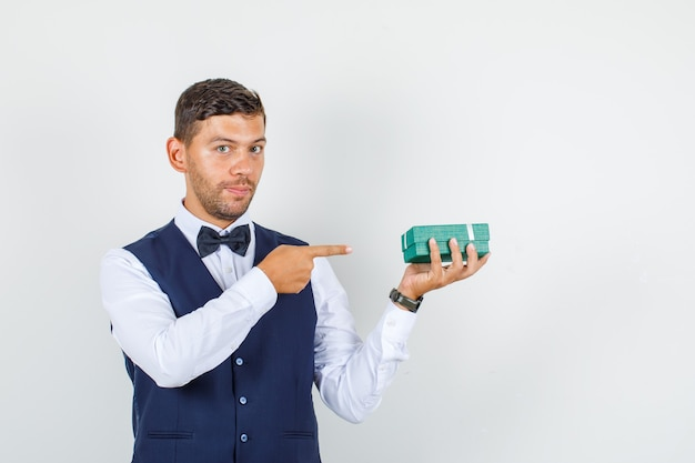 Kellner zeigt auf geschenkbox in hemd, weste und sieht selbstbewusst aus. vorderansicht.