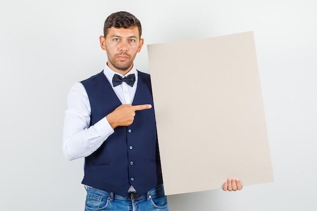 Kellner zeigt auf leere leinwand in hemd, weste, jeans und sieht ernst aus. vorderansicht.