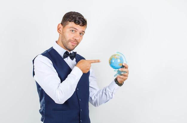 Kellner zeigt auf weltkugel in hemd, weste und schaut optimistisch, vorderansicht.