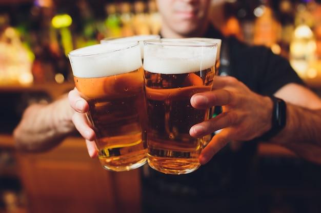 Kellnerhände, die ein lager-bier in ein glas gießen.
