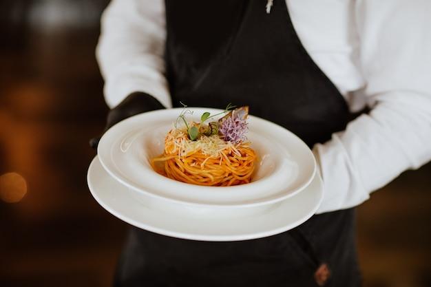 Kellnerhände, die frische spaghetti mit meeresfrüchten auf weißem teller im restaurant halten.