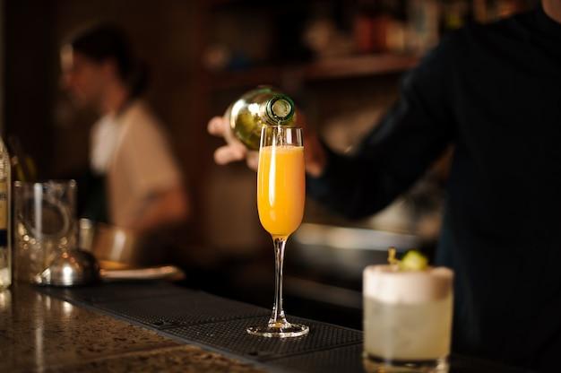 Kellnerhand, die ein frisches und helles orangengetränk in ein glas gießt