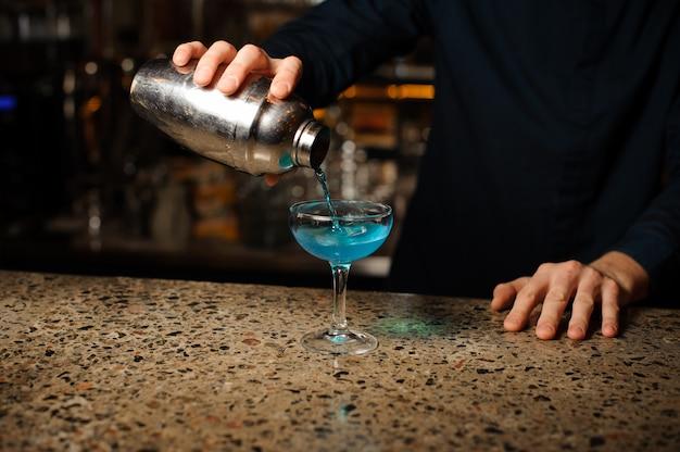 Kellnerhand, die neues getränk mit blauer flüssigkeit von einem schüttel-apparat in ein glas unter verwendung des siebs gießt
