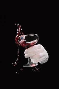 Kellnerhand in einem weißen handschuh, der ein glas mit rotwein mit augen, spritzern und getränkewellen auf schwarzem hintergrund schüttelt, halloween-konzept.