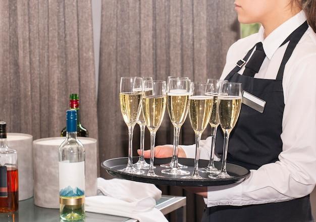 Kellnerin auf einem tablett mit champagner