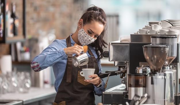 Kellnerin bereitet capuccino in einem café zu und trägt eine schützende gesichtsmaske.