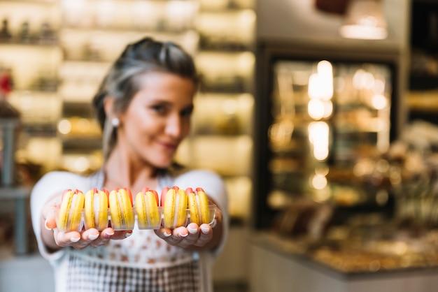 Kellnerin bietet macarons an