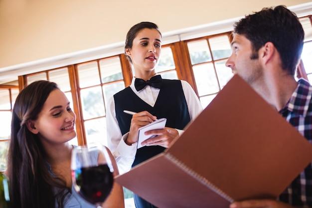 Kellnerin, die eine bestellung von einem paar entgegennimmt