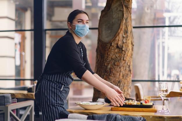 Kellnerin, die eine gesichtsmaske trägt, bedient kunden in einem café. coronovirus und schutz