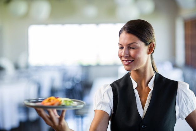 Kellnerin, die eine platte in einem restaurant hält