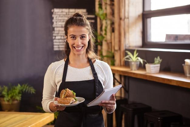 Kellnerin, die eine platte und ein klemmbrett hält