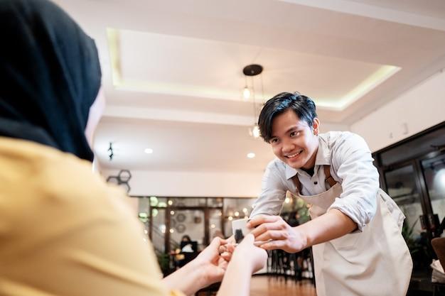 Kellnerin, die eine tasse kaffee für kundin im coffeeshop anbietet