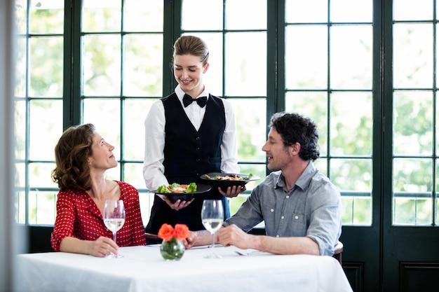 Kellnerin, die einem paar mahlzeit serviert