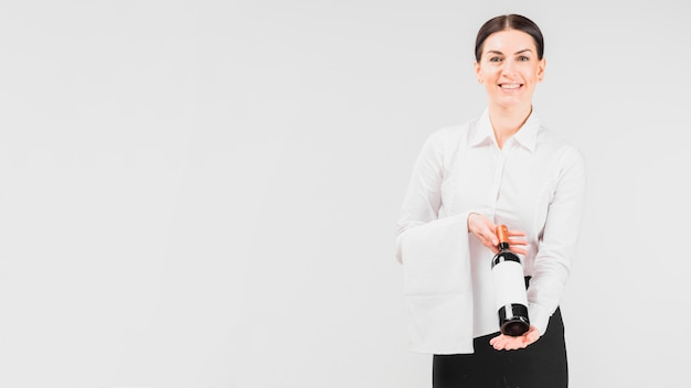 Kellnerin, die flasche wein lächelt und durchlöchert