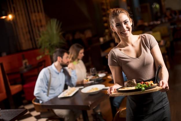 Kellnerin, die gruppe von freunden mit essen im restaurant dient